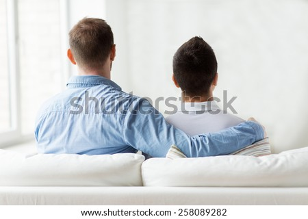 people, homosexuality, same-sex marriage, gay and love concept - close up of happy male gay couple or friends hugging from back at home - stock photo