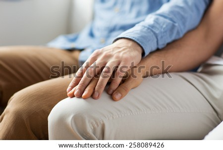 people, homosexuality, same-sex marriage, gay and love concept - close up of happy male gay couple holding hands - stock photo