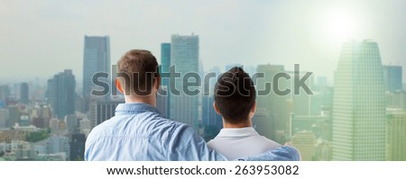 people, homosexuality, same-sex marriage, gay and love concept - close up of happy male gay couple or friends hugging from back over city background - stock photo
