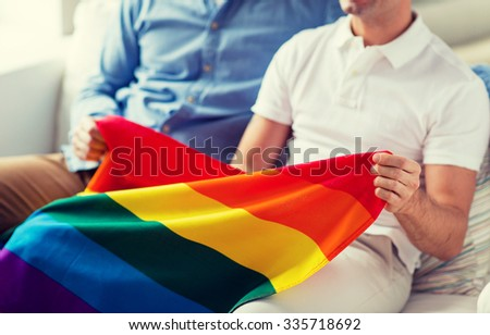 people, homosexuality, same-sex marriage, gay and love concept - close up of happy male gay couple hugging and holding rainbow flag at home - stock photo