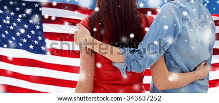 people, homosexuality, same-sex marriage, gay and love concept - close up of happy women couple hugging over american flag background over snow effect - stock photo