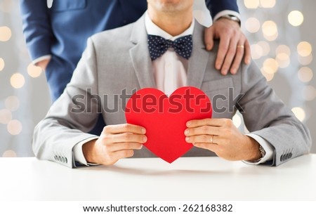 people, homosexuality, same-sex marriage, valentines day and love concept - close up of happy married male gay couple with red paper heart shape on wedding over holidays lights background - stock photo