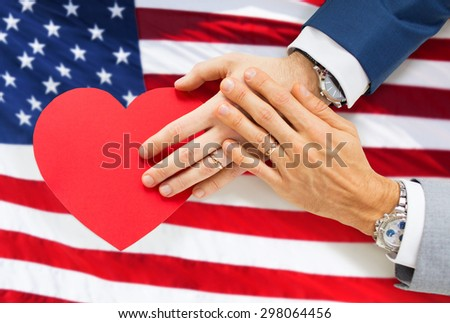 people, homosexuality, same-sex marriage, valentines day and love concept - close up of happy married male gay couple hands with red paper heart shape over american flag background - stock photo