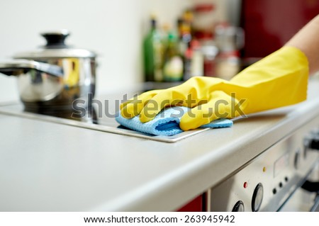 people, housework and housekeeping concept - close up of woman hand in protective glove with rag cleaning cooker at home kitchen - stock photo