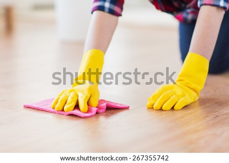 people, housework and housekeeping concept - close up of woman in rubber glover with cloth cleaning floor at home - stock photo