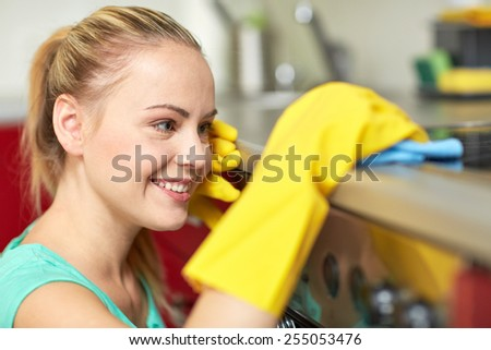 people, housework and housekeeping concept - happy woman cleaning cooker at home kitchen - stock photo
