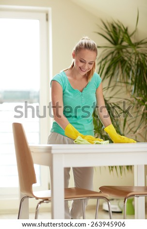 people, housework and housekeeping concept - happy woman cleaning table at home kitchen - stock photo