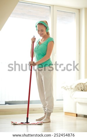 people, housework and housekeeping concept - happy woman in headphones listening to music and cleaning floor with mop at home - stock photo