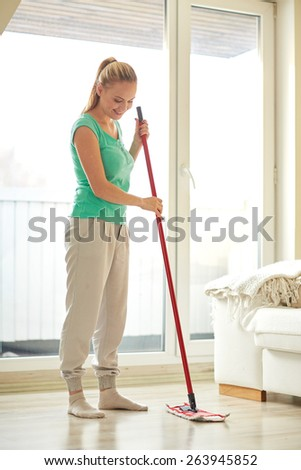 people, housework and housekeeping concept - happy woman with mop cleaning floor at home - stock photo