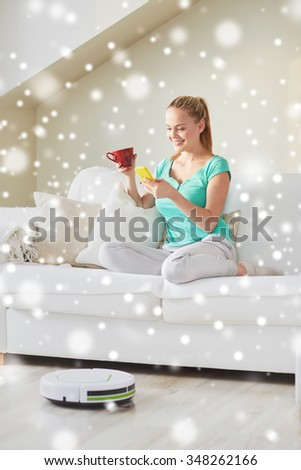 people, housework and technology concept - happy woman with smartphone and robot vacuum cleaner drinking tea at home over snow effect