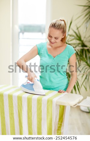 people, housework, laundry and housekeeping concept - happy woman with iron and ironing board at home - stock photo