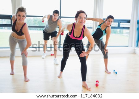 People in aerobics class lifting weights in fitness studio - stock photo