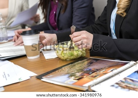 People in business formal outfit eating