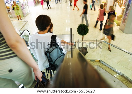 People in escalators at the mall. No brand names or recognizable faces. - stock photo