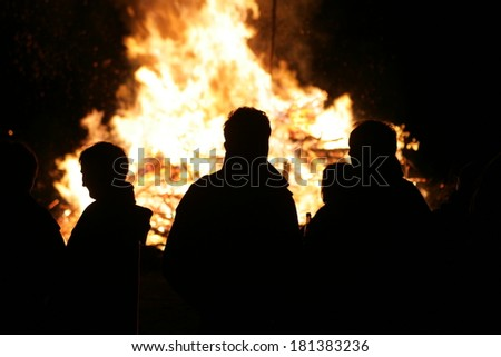 people in front of a burning woodpile a german tradition