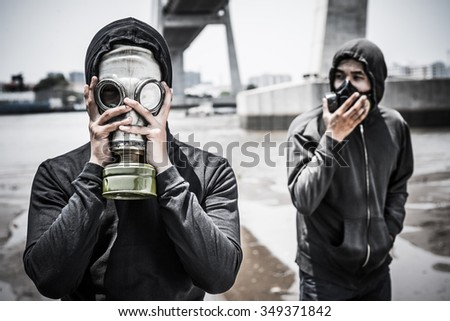 People in gas mask in the polluted city - stock photo