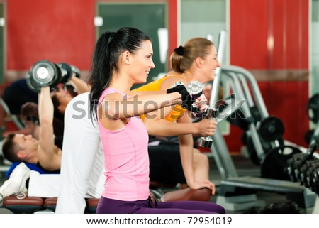 People in gym or fitness club exercising with weights together - stock photo