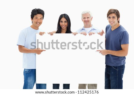 People in jeans holding and showing a big sign against white background