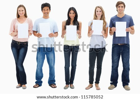 People in jeans holding five signs against white background