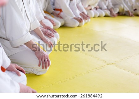 People in kimono sitting on tatami on martial arts training - stock photo