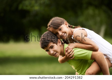 People in love with happy little girl and boy running piggyback in city park. Copy space - stock photo