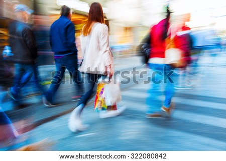 people in motion blur on the move in a shopping street of a city - stock photo
