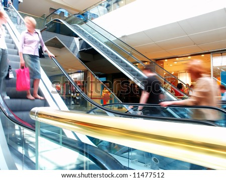 People in motion in escalators at the mall, with a golden banister at the foreground. - stock photo