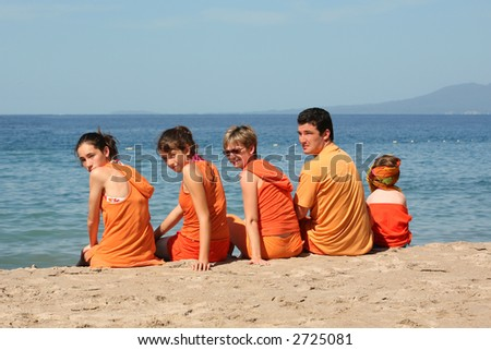 People in orange clothes on the beach - stock photo