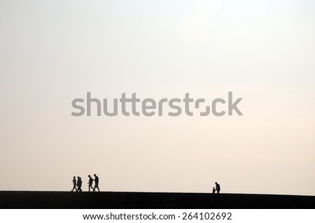 People in silhouette on Cobb harbour wall  - stock photo