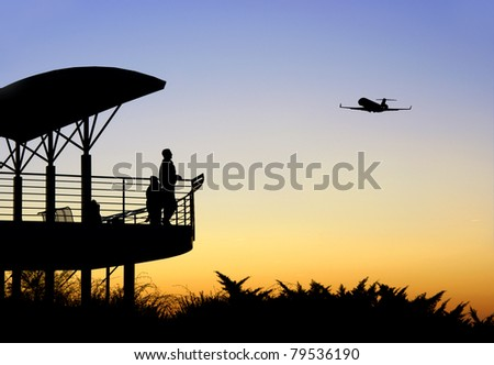 People in silhouette watching an airplane take off - stock photo