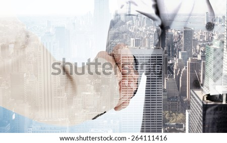 People in suit shaking hands against city skyline - stock photo