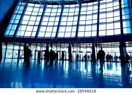 People in wide blue hall window in exposition center, left copmosition - stock photo