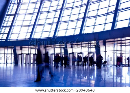 People in wide violet hall window in exposition center, left copmosition - stock photo