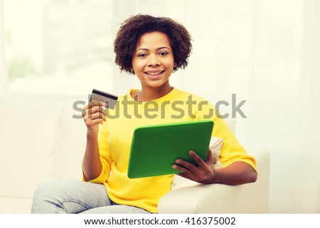 people, internet bank, online shopping, technology and e-money concept - happy african american young woman sitting on sofa with tablet pc computer and credit card at home - stock photo