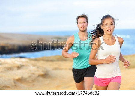 People jogging for fitness running in beautiful landscape nature outdoors. Woman and man sports athletes training cross-country trail running. Couple together, Asian woman, Caucasian man, - stock photo