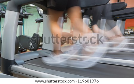 People jogging on a treadmill in the gym - stock photo