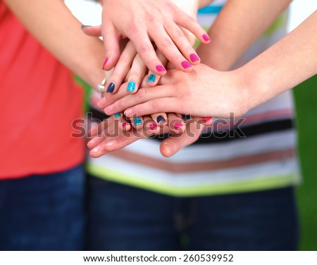 People joining their hands  standing on green grass - stock photo