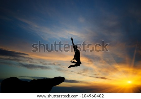 people jumping from the top of the mountain on the background of the sunset