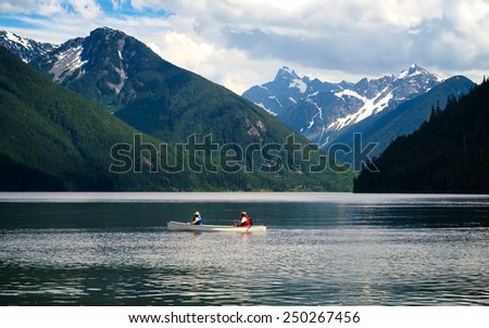 People kayaking on a lake in the mountains. Activities on the water. Chillwack Lake, BC (CANADA) - stock photo