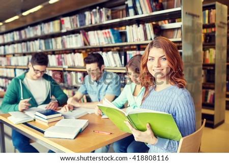 people, knowledge, education and school concept - group of happy students reading books and preparing to exam in library - stock photo