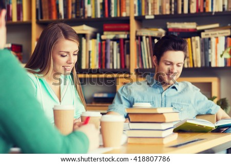 people, knowledge, education and school concept - group of happy students reading books, drinking coffee and preparing to exam in library