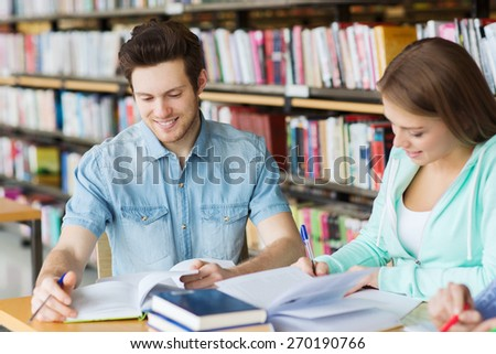 people, knowledge, education and school concept - group of happy students with books preparing to exam in library - stock photo