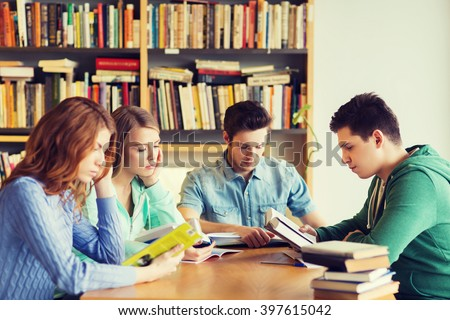 people, knowledge, education and school concept - group of students reading books and preparing to exam in library - stock photo
