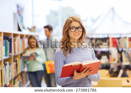 people, knowledge, education and school concept - happy student girl or young woman with book in library - stock photo