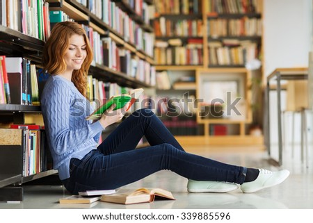 people, knowledge, education and school concept - happy student girl sitting on floor and reading book in library - stock photo