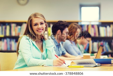 people, knowledge, education and school concept - happy student girl writing to notebook in library - stock photo