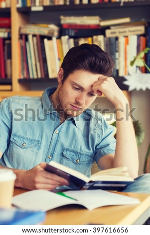 people, knowledge, education and school concept - male student reading book in library - stock photo