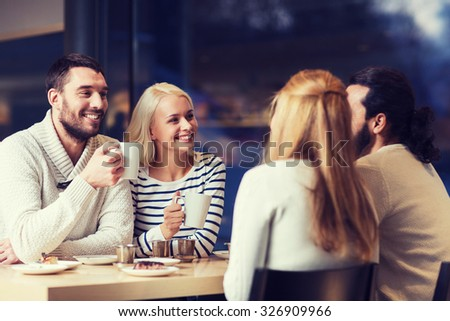people, leisure, communication, eating and drinking concept - happy friends meeting and drinking tea or coffee at cafe - stock photo