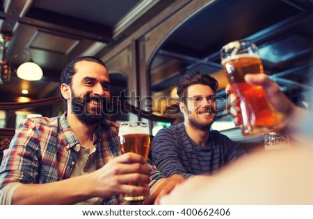 people, leisure, friendship and and bachelor party concept - happy male friends drinking beer at bar or pub - stock photo