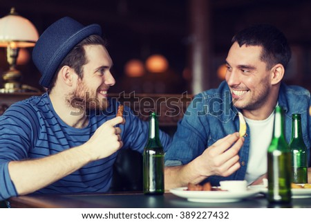 people, leisure, friendship and bachelor party concept - happy male friends drinking bottled beer and talking at bar or pub - stock photo